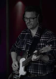 Guitarist Peter Gunnebro records his electric guitar in the studio