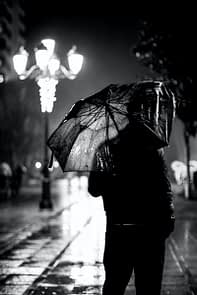 """Sad person walking with umbrella in the pouring rain. Descriptive picture of Tailor Hill Stations song """"October Rain""""."""