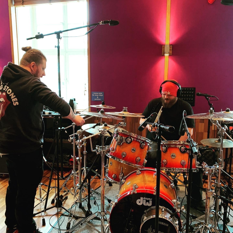 Studio team prepares the drumset in the studio for recording