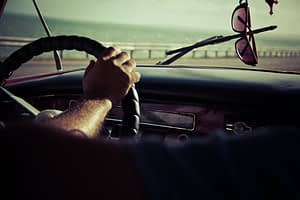 Picture of a man with his hands on steering wheel. Shades hanging in rear mirror.