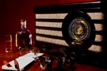 A picture of an old radio, a bottle of whiskey and a pair of glasses