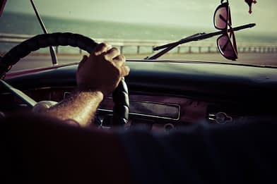 """Girl Guy driving behind the steering wheel driving his car on the American highway. Shades on dashboard. Descriptive picture of Tailor Hill Stations song """"Leaving My Safe Zone""""."""