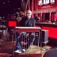A picture of steel guitarist Travis Toy sitting by his pedal steel guitar at Grand Ole Opry in Nashville.